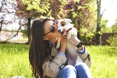 Jeune femme attirante de hippie dans des lunettes de soleil embrassant le chiot de terrier de Russell de cric au parc, à la pelou Image stock