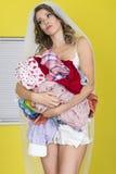 Jeune femme attirante de jeune mariée tenant la blanchisserie sale Thoughful photos stock