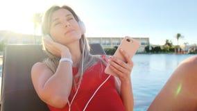 Jeune jeune femme attirante de sourire dans la musique de écoute de bikini rouge de son smartphone dans des écouteurs blancs, tou banque de vidéos