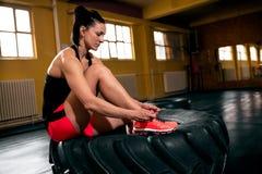 Jeune femme attirante de sports s'asseyant sur de grandes chaussures de pneu et de grippage Photo libre de droits