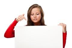 Jeune femme attirante derrière le panneau vide sur le fond blanc photos libres de droits