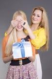 Jeune femme attirante donnant un présent à son ami étonné Photo stock