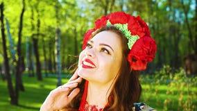 Jeune femme attirante en costume de folklore et anneau de fleur souriant à la caméra clips vidéos