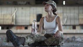 Jeune femme attirante en eau potable d'uniforme militaire de la bouteille se reposant sur le plancher dans sale poussiéreux aband banque de vidéos
