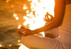 Jeune femme attirante en position de yoga sur une belle plage photos stock