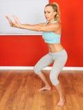 Jeune femme attirante exécutant des postures accroupies d'exercice Image stock