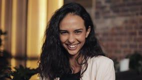 Jeune femme attirante examinant la sensation de sourire de caméra heureuse dans la fin confortable de café  banque de vidéos
