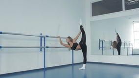 Jeune femme attirante faisant étirant la séance sur le yoga de floorfor, dans une salle lumineuse de couleur de salle de gymnas clips vidéos