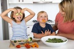 Jeune femme attirante faisant cuire ainsi que peu 3 et 7 années jouer de fils et de fille heureux avec la tige de concombre comme Photos stock