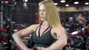 Jeune femme attirante faisant l'exercice avec le poids dans le gymnase banque de vidéos