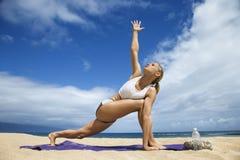Jeune femme attirante faisant le yoga sur la plage Photographie stock libre de droits
