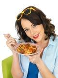 Jeune femme attirante heureuse tenant un plat des boulettes de viande de spaghetti images stock
