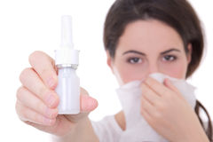 Jeune femme attirante jugeant la pulvérisation nasale d'isolement sur le blanc Photographie stock