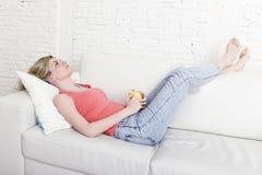 Jeune femme attirante jugeant la tasse de café se reposant sur le sourire de divan de sofa à la maison heureuse Photo stock