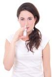 Jeune femme attirante à l'aide de la pulvérisation nasale d'isolement sur le blanc Images stock
