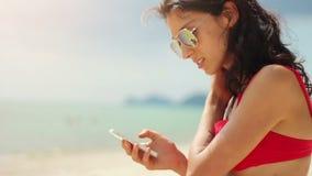 Jeune femme attirante à l'aide de son téléphone sur la plage banque de vidéos