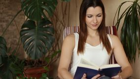 Jeune femme attirante lisant le livre intéressant tout en se reposant sur la chaise confortable dans le salon Sourit tandis que clips vidéos