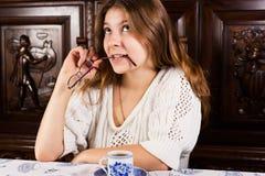 Jeune femme attirante malfaisante tenant des verres, rêvant Image stock