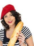 Jeune femme attirante mangeant un pain français de pain de bâton Photos libres de droits