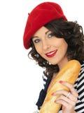 Jeune femme attirante mangeant un pain français de pain de bâton Image stock