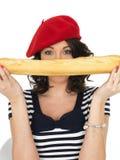 Jeune femme attirante mangeant un pain français de pain de bâton Photographie stock libre de droits