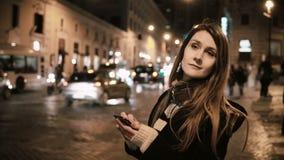 Jeune femme attirante marchant au centre de la ville, près de la route du trafic et à l'aide du smartphone avec l'écran tactile clips vidéos