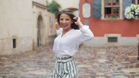 Jeune femme attirante marchant sur la rue après regard de pluie à la caméra tournant l'eau mignonne de mode de sourire heureux clips vidéos