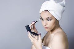 Jeune femme attirante mettant sur le renivellement photo stock