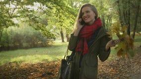 Jeune femme attirante parlant au téléphone portable en beau parc d'automne banque de vidéos