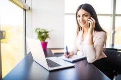 Jeune femme attirante parlant au téléphone portable et souriant tout en se reposant à son lieu de travail dans le bureau et regar Photographie stock