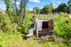 Jeune femme attirante près du puits d'eau en bois Image stock