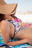 Jeune femme attirante prenant un bain de soleil tout en se trouvant sur un essuie-main de plage Photo libre de droits