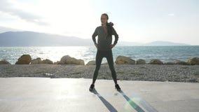 Jeune femme attirante réchauffant avant le fonctionnement sur la plage banque de vidéos
