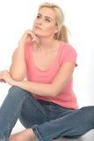 Jeune femme attirante réfléchie heureuse s'asseyant sur la détente de plancher Image libre de droits
