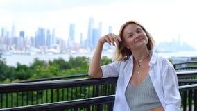 Jeune femme attirante regardant à la caméra et souriant sur le fond de New York City banque de vidéos