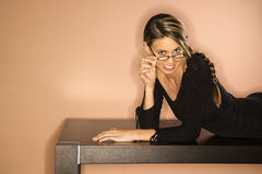 Jeune femme attirante regardant au-dessus de son SM en verre Photo stock