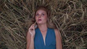 Jeune femme attirante s'étendant dans le domaine de blé d'or Sa main est oreille émouvante de blé Concept de moisson Moisson clips vidéos