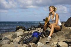 Jeune femme attirante s'asseyant avec la bicyclette sur le Roc Photos stock