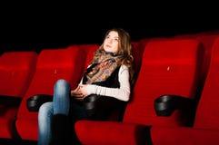 Jeune femme attirante s'asseyant dans un cinéma Photographie stock