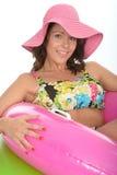 Jeune femme attirante s'asseyant en anneaux en caoutchouc utilisant un maillot de bain photo libre de droits