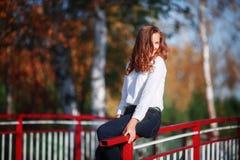 Jeune femme attirante s'asseyant en parc coloré d'automne Photo stock