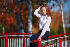 Jeune femme attirante s'asseyant en parc coloré d'automne Image stock