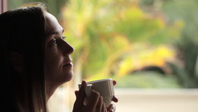 Jeune femme attirante s'asseyant près de la fenêtre et du thé potable banque de vidéos