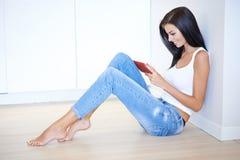 Jeune femme attirante s'asseyant sur l'étage Photo libre de droits