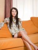 Jeune femme attirante s'asseyant sur le sofa Image libre de droits