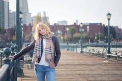 Jeune femme attirante sûre sur le pont en bois semblant décontracté Image libre de droits