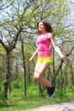 Jeune femme attirante sautant avec une corde à sauter en été Photos libres de droits