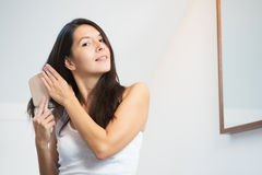 Jeune femme attirante se brossant les longs cheveux Photos stock