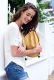 Jeune femme attirante se penchant contre la barrière tenant le chapeau de cowboy photographie stock