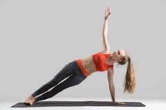 Jeune femme attirante se tenant dans la pose latérale de planche, studio gris Photographie stock libre de droits